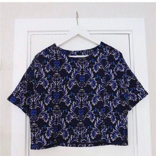 Snygg kort mönstrad blå topp/T-shirt från BIK BOK. Så snyggt mönster och passform! Slutsåld, passa på att fynda till lågt pris! Säljer likadan i annat mönster. Passar fler storlekar beroende på hur man vill att den ska sitta! Storlek M.