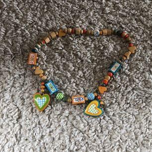 Halsband med olika färger i trä. Elastiskt.
