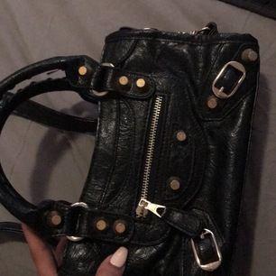 Intressekoll på denna jätte fina svarta Balenciaga inspirerade väskan den är i väldigt fint skick, och passar till det mesta :) 1x axelband (frakt: 63kr skickas spårbart)