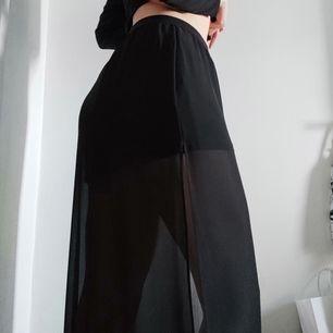 En svart lång kjol med två slits på varsin sida av kjolen. En tillhörande underkjol av svart tyg som sitter fast samt ett skönt resårband längst upp 🌞 fint och luftigt till sommaren! För referens är jag 177cm. Köparen står för frakt.