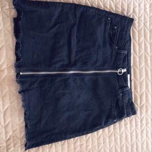 Svart jeanskjol med en dragkedja som kan öppnas upp helt. Kjolen är från esprit och är strl 36