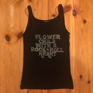 """Flower Child With A Rock ⭐️ Roll Heart"". Målat linne svart med ljust gul text. Tar swish. Frakt ingår. 🤗"