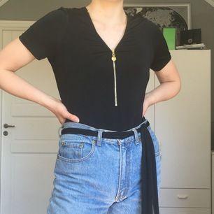Dragkedjan går att dra upp och ner. Det medföljer ett skärp som är menat att vara runt tröjan. Man kan även ha det som skärp i byxorna som jag har på bilden 😊. Materialet är glansigt och svalt.