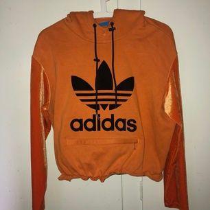 Omgjord Adidas hoodie, inköpt från Zalando. Croppad modell med resår i midjan och ficka med dragkedja på magen. Ärmarna är i sammetsliknande material. Märke efter gammal söm på baksidan, se bild 3. Möts upp i Stockholm alt. köparen står för frakt!🧡