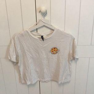 En vit t-shirt med tryck från h&m i storlek S. Jätteskön och luftig tröja som slutar vid midjan. Jag säljer den för att den blivit för liten🍕köparen står för frakten!