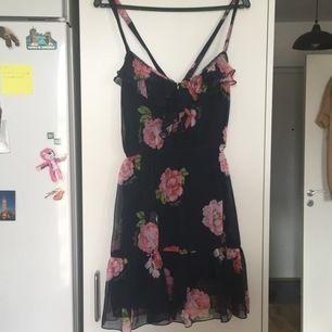Mörkblå klänning med knappar framtill. Perfekt att ha på sommaren. Kors i ryggen av axelbanden fastsydd mörkblå underklänning.