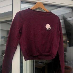 Röd tröja med en broderad ros från pull&bear. Ingen magtröja men är lite kortare i modellen 😊