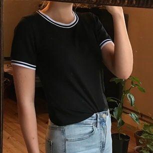 Svart T-shirt i lätt material med vita ränder vid båda ärmarna och vid urringningen. Köpt på BikBok. Buda!