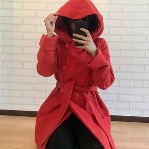 Det är en röd kappa i storlek 36 från Ellos. Den är i bra skick och har en väldigt fin färg. Den är varm och har mycket plats. Den ger en jättefin silhouette och har en luva. Perfekt för vintern.