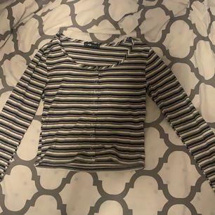 Ribbad tröja från New Yorker svart, vit, grå och rosa randig. Knappar.