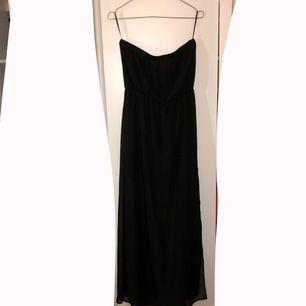 Svart golvlång klänning med slits på sidan. Svart tajt kjol under golvlång chiffong. Strl 40. Använd ett fåtal gånger, fint skick! Köparen står för frakten! ⭐️