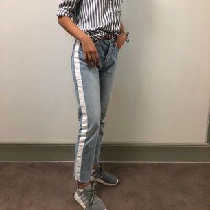 Säljer dessa otroligt snygga mom jeans med en vit stripe på varsinn sidan i mycket bra skick🤩 Stl 34. Pris 300kr:)