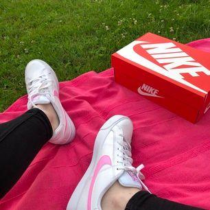 Helt oanvända vita Nikes med rosa swoosh, endast testade för bilden. Liknar air force men inte lika grov sula. Väldigt bekväma skor! Nike-lådan medföljer gratis. Frakt tillkommer, kan skicka fler bilder i DM. 🌸🌸🌸 Pris eller högsta bud som gäller!