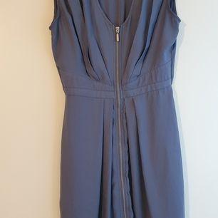 Ljusblå klänning från H&M, knälång, definierad midja, v-ringad, med dragkedja längs hela framsidan som går att öppna, storlek 36