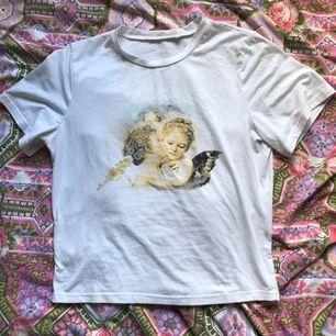 Supercute vit T-shirt med änglar på i vintagestil. Sparsamt använd och i jättefint skick. Ryggen är helvit. Storleksmärkt som medium men jag har använt den som oversized (jag har small). Vid frakt står köparen för kostnaden 👼🏻