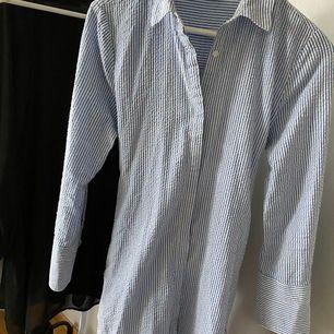 Lång blå randig skjorta med knut, kan knytas fram eller bak. Använd 1-2 gånger, i nyskick. 200 kr inkl frakt.