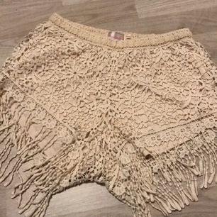 Söta beige shorts med blommig mönster och tofsar ner till, i storlek S. Perfekt till en promenad på stranden 🏖💖