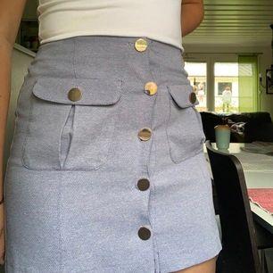 Lila/blå minikjol med guldfärgade knappar, fickorna är riktiga och går att använda! 40kr+frakt
