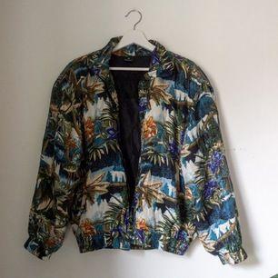 Fin tunn vintage jacka med härligt mönster i bombermodell. Med muddar och två praktiska fickor. I fint skick! Utsidan 100% silke och foder 100% polyester. Obs! Saknar dragkedja, jag har använt den öppen, det går att sy på en lätt om en vill.