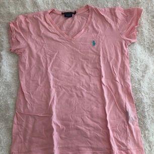 Rosa Ralph lauren T-shirt med ljusblått märke. Storlek XS men kan passa en mindre S där den kommer sitta lite tightare. Inte mycket använd, dock skrynklig på bilden då den var nytvättad.