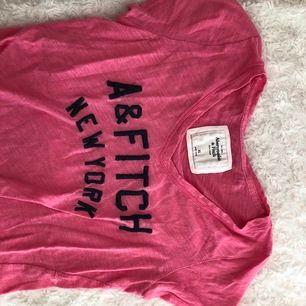 Ljusrosa abercrombie & Fitch T-shirt med mörkblå text. Storlek XS men otroligt stretchigt material och också uttöjt så skulle säga att det definitivt är en S och eventuellt passa en mindre M.