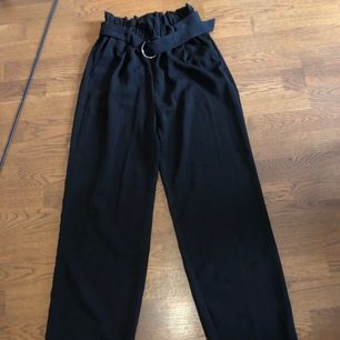 Svarta kostymbyxor med bälte i midjan. Sömmarna längst ner har släppt men kan du sy upp byxor så borde det inte vara något problem. Köpare står för frakt