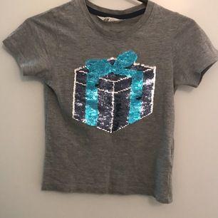 Helt ny superfin t-shirt  för både flicka och pojke ålder 5-6 med paljett magiskt  motiv som du kan variera i paketet gömmer sig en dinosaurer (se foton ) du drar vara med handen över paljett  mönster :) jag postar allt jag säljer i priset ingår frakt.