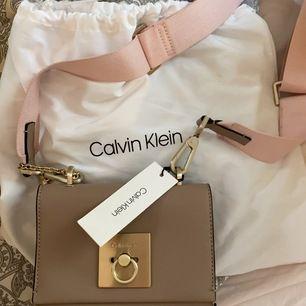 Liten Calvin Klein väska i färgen mörk beige med rosa band aldrig använd bra skick köpt för 1500kr säljes för  700