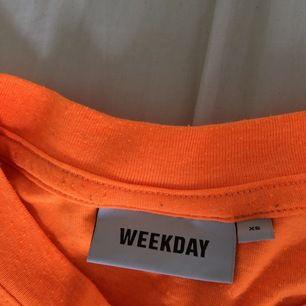 en neon orange t-shirt i storlek xs från weekday. köpt förra sommaren. Ganska knottrig. Går att använda som klänning.