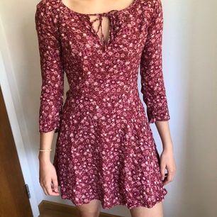 Mönstrad klänning i röda nyanser med 3/4 långa ärmar från Hollister. (Storlek står ej i klänningen) 65kr+frakt