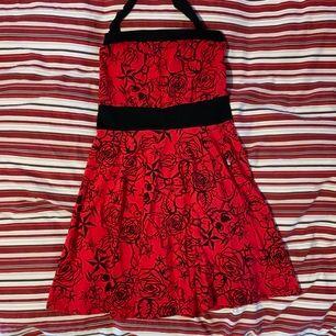 """Rockabilly klänning, röd med dödskallar och rosor. Man knyter runt halsen. Aldrig använd, bara hänt i garderoben. Strl M/L. Tyget är töjbar och """"luftig"""". Frakt tillkommer!"""