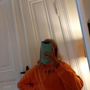 En fin orange hoodie från H&M med texten Nasa och text på armarna, den var köpt i Januari och är använd 4 gånger. (80kr+22kr frakt)