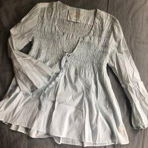 Ser vit ut på bilden men tröjan är ljusblå. Luftig och skön! Storlek M. Köparen står för eventuell frakt.