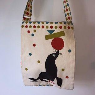 Väska från Tinou le Joly Sénoville. Stängs med magnet. Längden på axelremmen kan regleras. Väskan är ca 40 cm hög. Mycket fint skick! Köparen står för frakten🧡