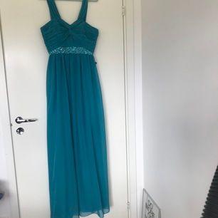 Säljer en jättefin klänning som passar perfekt till bal, den är blå/turkos (teal)  i storlek 40 från Nelly med alla lappar kvar då den är oanvänd
