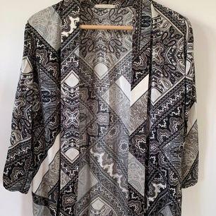 Klassisk och fin kimono som både passar att klä upp eller ha på stranden. Utmärkt skick!
