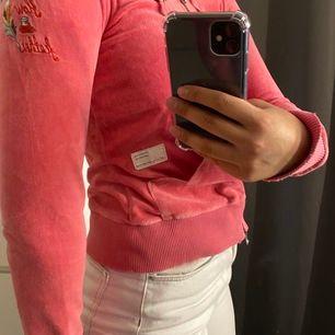 En rosa odd Molly kofta i storlek 1, sitter som en XS med en snygg broderad fjäril på ryggen.
