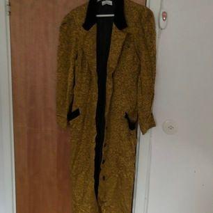 Lång kappa i gul-guldig färg med svarta detaljer. Köpt på second hand. Måste sälja den är för liten på mig :(