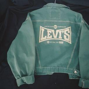 Häftigaste vintage Levi's jeansjackan med stort tryck på ryggen och i en härlig grönblå färg med kontrasterande vita sömmar! Passar en storlek S perfekt lite oversize, den är ganska kort ryggen så rumpan syns ;) Tvättas och stryks innan leverans! 💫💫