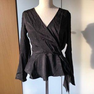 Söt omlottblus med diskret mönster. Blusen är från H&M och i storlek 42, vilket passar dig som klär dig i M. Aldrig använd, prislappen sitter kvar!!
