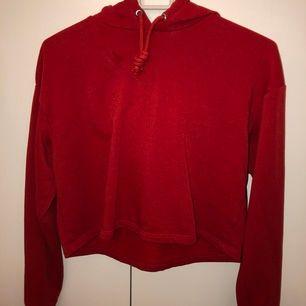 En röd croppad tröja från H&M, har använts 1 gång. Har även en luva där bak. Storlek XS men passar även S. Ordinarie pris: 100 kr