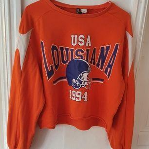 Croppad orange sweatshirt från H&M 🧡 tryck på framsidan och vita detaljer på ärmarna ⭐ ca 3 år gammal men i bra skick. Storlek S och är ganska oversized. Säljs då den inte används längre. Kontakta vid frågor/intresse 💜 frakt tillkommer