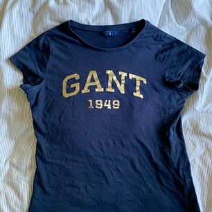 Gant T-shirt i färgen marinblå med guldig text. Använd men super fint skick. Storlek XS. Priset är diskuterbart. 🌸