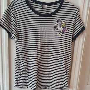 Marinblå- och vitrandig t-shirt med en enhörningspatch från H&M ⭐ väldigt stretchigt material vilket gör den väldigt bekväm. Storlek M :) Lite sliten men bra skick. Säljs då den inte längre används. Kontakta vid frågor/intresse 💜 frakt inräknad