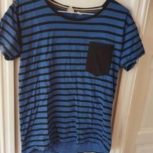 Blå & svartrandig t-shirt med ficka. Storlek S i herrmodell och är därför väldigt stor. Använts som pyjamaströja, men fungerar till vardags också ⭐ Säljs då den inte används längre. Kontakta vid frågor/intresse 💜 frakt tillkommer