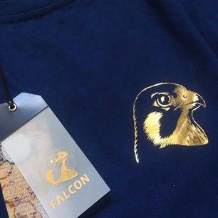 Bli coolast på festen!🦅 Marinblå tröja med loggan på bröstet och texten Falcon i guld på högra ärmen🤩 Såldes i Falcons webbshop, går inte att köpa längre! I nyskick, med lapparna kvar. Ett måste för ölälskaren🍻 Strl s i herr fit