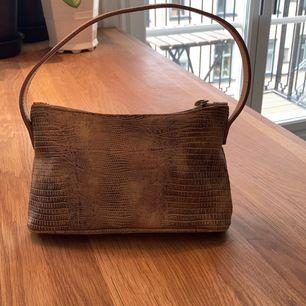 En snygg väska man kan ha sin mobil och plånbok i.