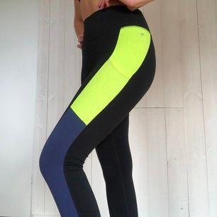 Ett par snygga träningstights från Fabletics. Har fickor på sidan (se bild två) som är väldigt användbart när man springer eller är på gymmet osv. Har detaljer i neon (samma färg på Kappa skorna som jag säljer i en annan annons) och mörkblått.