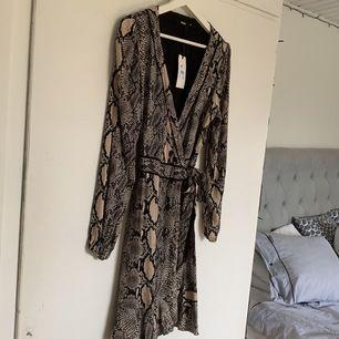 En supersöt klänning från BikBok i storlek M men passar även S eftersom man själv kan dra åt den i midjan. Klänningen är helt oanvänd och lappen finns fortfarande kvar. Nypris var 499kr men mitt pris är 120kr🤎🤎
