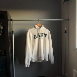 En vit hoodie från Gant med marinblå text. Tröjan är i bra skick. Finns en minimal fläck bredvid en av bokstäverna som knappast syns. Men be gärna om bild :) Denna modell går ej att få tag på men köptes för 1099kr